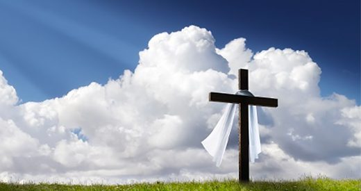 Photograph of a cross on a hill with clouds behind
